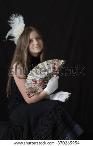 A young caucasian girl dressed in black with a white feather hair pin, white gloves, and a spanish/oriental fan. All with a dramatic black background and lovely natural lighting. Vertical format. - stock photo