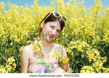A young caucasian girl in a field of spring canola flowers. - stock photo