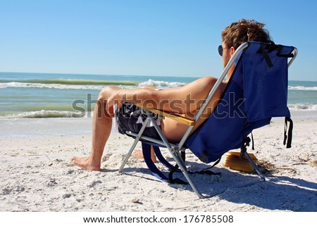 a young caucasian man has been reading a book and is now lounging in a beach chair and sunbathing by the ocean - stock photo