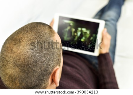 a young caucasian man lying on the couch watches a movie or a series in streaming in his tablet computer - stock photo