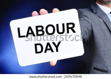 a young caucasian man wearing a gray suit shows a signboard with the text labour day written in it - stock photo