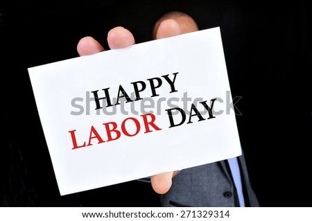 a young caucasian man wearing a grey suit shows a signboard with the text happy labor day written in it, against a black background - stock photo