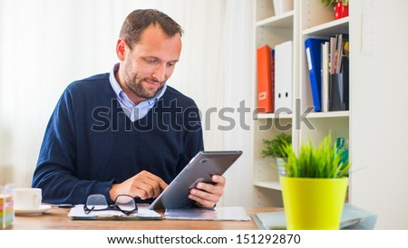 A young caucasian man with tablet in his office. - stock photo