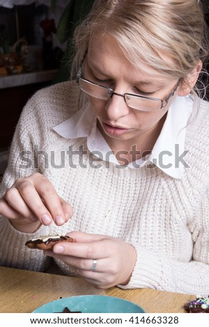 A Young caucasian woman decorating cookies - stock photo