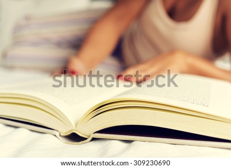 a young caucasian woman in pajamas reading a book in bed - stock photo