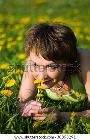 A young cheerful woman having fun on a dandelions glade
