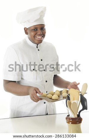 A young chef happily carrying a cookie sheet of dough balls to bake them in the oven.  On a white background. - stock photo