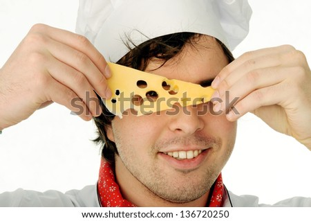 A young chef  looking through the cheese hole - stock photo