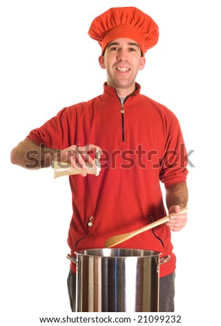 A young chef wearing red is adding some ground pepper to his pot of soup
