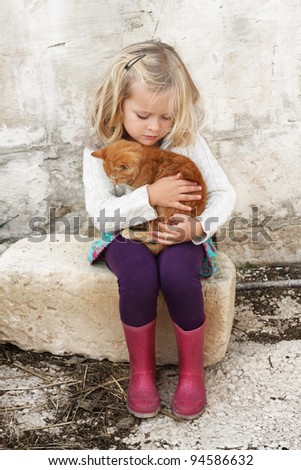 A young child hugging a small kitten, very tender moment, lots of love - stock photo