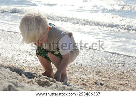 A young child is crouching down looking for seashells to pick up on a white sand beach by the ocean at sunset, while on summer vacation.
