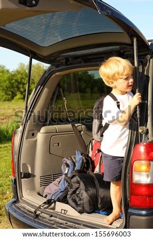 a young child is standing in the back of his minivan with a backpack on, looking outside and waiting for his family to come for a summer camping vacation
