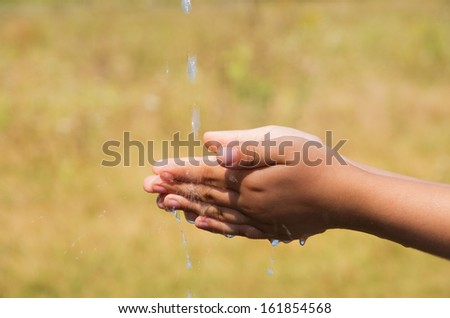 A young child is washing his hand. - stock photo