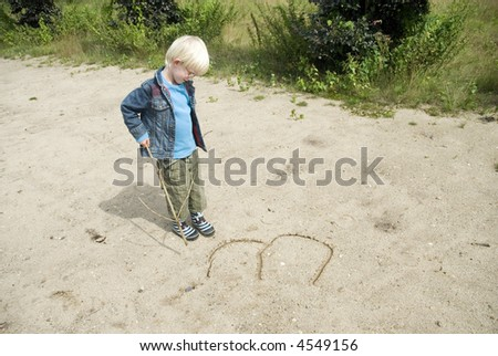 a young child is writing letters in the sand - stock photo