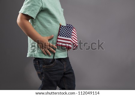 A young child plays with two American Flags. - stock photo