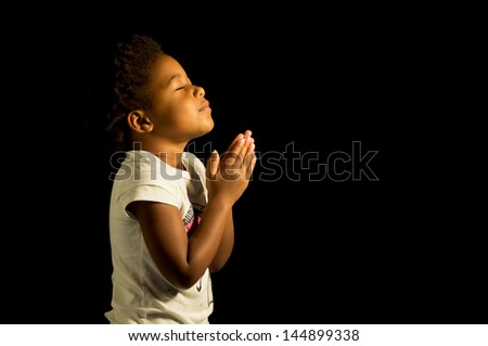 A young child prays to God. - stock photo