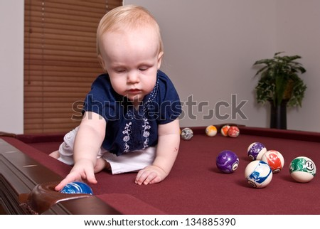 A young child sitting alone on a billiard table playing with the pool balls and dropping a blue ball in a side pocket. - stock photo