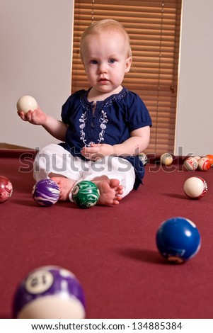 A young child sitting alone on a billiard table playing with the pool balls. She holds a cue ball in here hand and looks at the camera. - stock photo