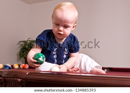 A young child sitting alone on a billiard table playing with the pool balls. She holds a green ball as she looks into the side pocket of the table.