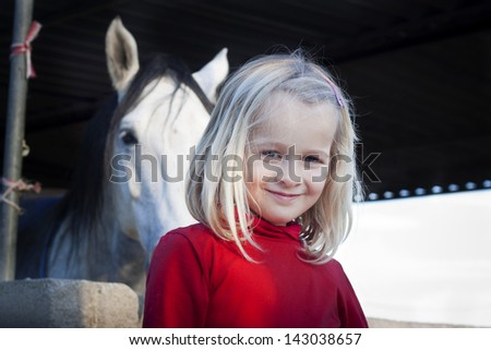 A young child standing in front of her horse, looking at the camera, positive feeling