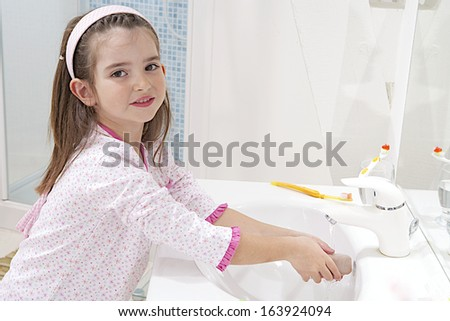 A young child washing her hands with soap. Healthy lifestyle