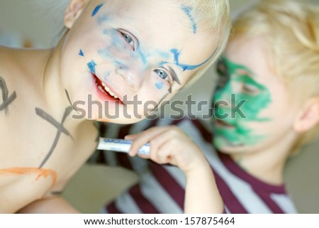 A young child with a green painted face is coloring his happy baby brother's face and skin with markers