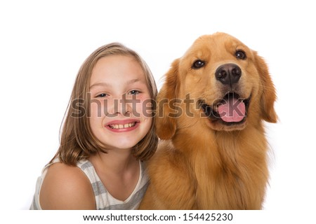 A young child with her golden retriever dog - stock photo