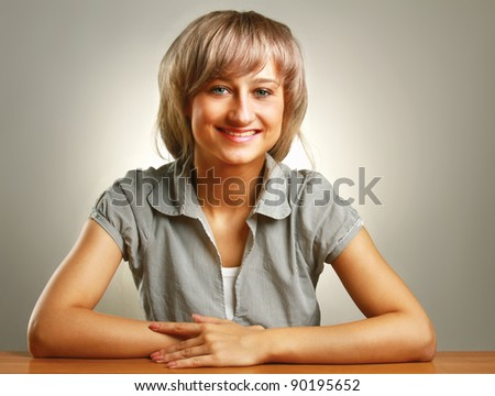 A young college girl sitting at the desk - stock photo