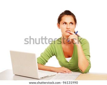 A young college girl sitting in front of a laptop, looking up, isolated on white background - stock photo