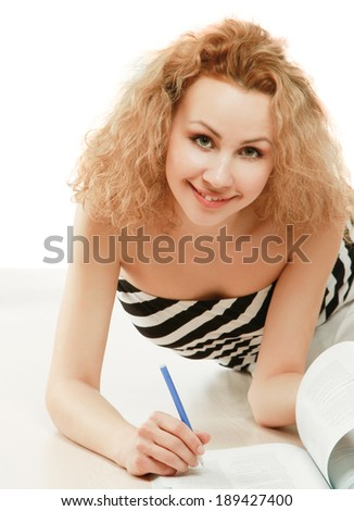 A young college girl with a book lying on the floor, isolated on white - stock photo