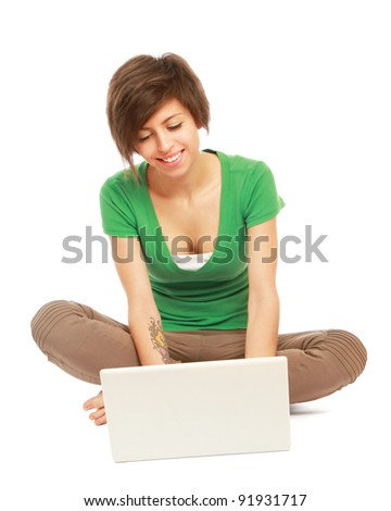A young college girl with a laptop, sitting on the floor, isolated on white background - stock photo