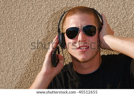 A young college student listens to music on some headphones