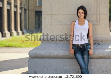 A young, confident girl stands near a wall, in waiting - stock photo