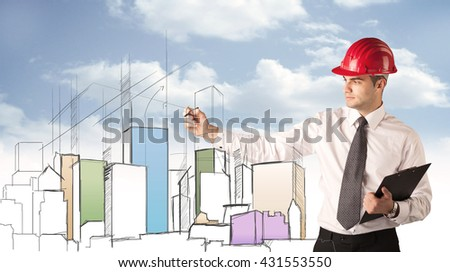 A young construction worker in a red safety helmet happily planning a city sight and drawing lines, arrows, angles, buildings with a pen in his hand - stock photo