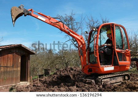 A young construction worker in an excavator is digging in a garden - stock photo
