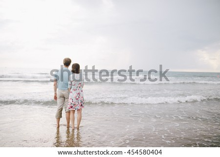 a young couple, a guy in a blue shirt and trousers, a girl in a dress standing on the beach and look at the ocean, romantic moment