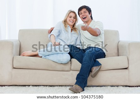 A young couple are sitting down on a couch looking at the camera and laughing - stock photo