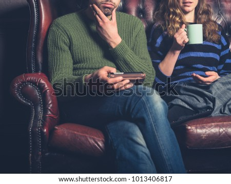 A young couple are sitting on a sofa at home using a smart phone and drinking tea