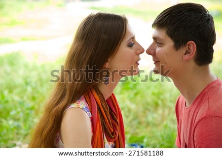 A young couple between 20 and 30 is looking at each other - stock photo