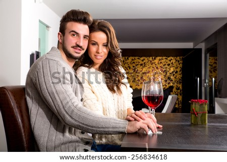A young couple enjoying a glass of wine at night time at home.