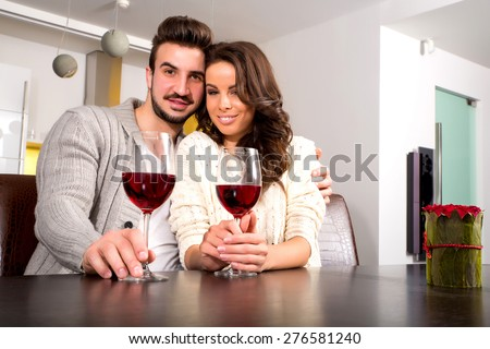 A young couple enjoying a glass of wine at night time at home.  - stock photo