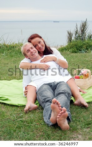 A young couple get cuddly during a romantic picnic. - stock photo