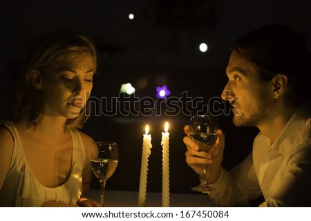 A young couple have a serious conversation over white wine at a candle lit table.  - stock photo