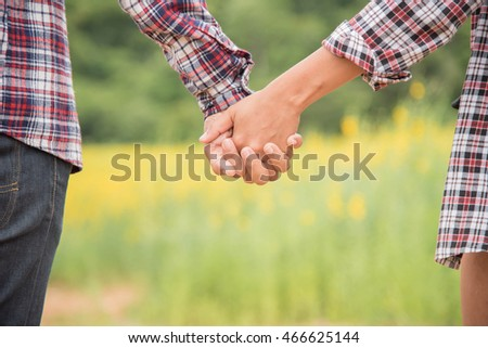 A young couple holding hands. In Nature