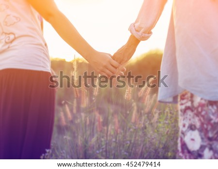 A young couple holding hands. In Nature sunrise - stock photo