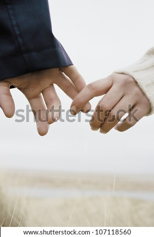 a young couple holding hands, outdoors - stock photo
