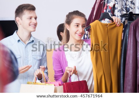 A young couple in a boutique chooses dress