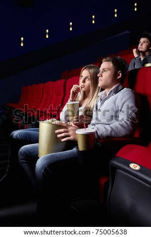 A young couple in a movie theater - stock photo