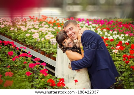 A young couple in love bride and groom, wedding day in summer. Enjoy a moment of happiness and love in a red flowers field