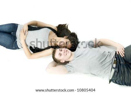 A young couple in love lying down together in a studio